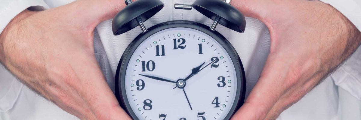 Doctor with alarm clock in hands, it is time to make an appointment for your next medical exam